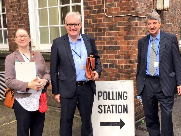 Norwegian Deputy Speaker Kenneth Svendson (R) and Belgium Senator Pol Van Den Driessche (L) visit a polling station in Lambeth with BGIPU's Sarah Crandall