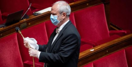 An usher cleans a mike in France's National Assembly. © Thomas SAMSON / AFP